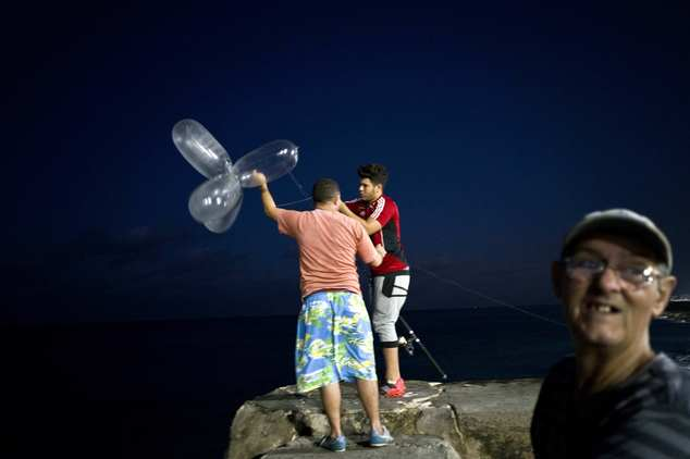 """This Nov. 12, 2016 photo shows Derek Aguiar Gonzalez, a stomatology student and amateur fisherman who said he takes home what he catches, preparing to cast his line, fitted with inflated condoms that serve to keep the bait high in the water and increase the line's resistance against the pull of heavy fish, at the malecon seawall in Havana, Cuba. Few are as creative as what Havana's fishermen call """"balloon fishing,"""" a technique employing a couple of cents worth of condoms to pull fish worth an average month's salary from the ocean. (AP Photo/Ramon Espinosa)"""