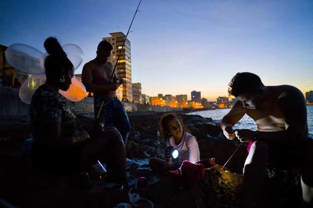 In this Nov. 13, 2016 photo, Edelmis Ferro Solano, far left, holds inflated condoms for her husband Junior Torres Lopez, standing behind her, to use on his fishing line as a bobber, while her granddaughter Leyanis Macias Puente helps out by shining a flashlight on the hook of family friend Fran Luis Martinez Nueva, as they fish along the malecon seawall in Havana, Cuba. According to the fishermen's lore, the inventor of the balloon technique in Cuba saw a video of South Africans fishing using kites and got the idea for using inflated condoms. (AP Photo/Ramon Espinosa)